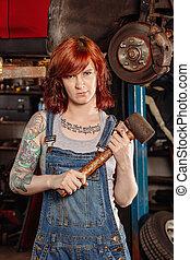 Female mechanic holding rubber mallet