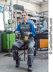 Female mechanic sitting in metal workshop looking into camera
