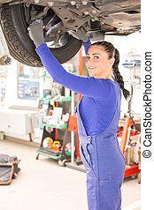 Female mechanic working on car on hydraulic ramp