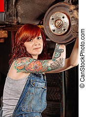 Female mechanic working under the car