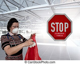 Female medic put infected waste into plastic bag on airport. STOP coronavirus sign.