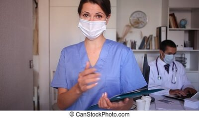 Female medical worker in protective face mask meeting staff in office. Concept of monitoring health status of employees during coronavirus pandemic. High quality FullHD footage