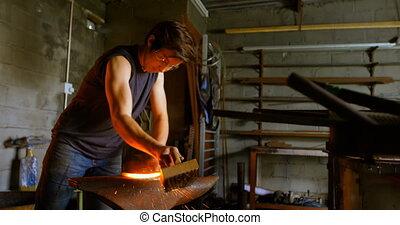 Female metalsmith brushing horseshoe in fire 4k - Attentive ...