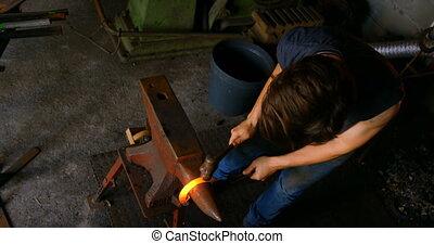 Female metalsmith molding horseshoe in factory 4k - Overhead...