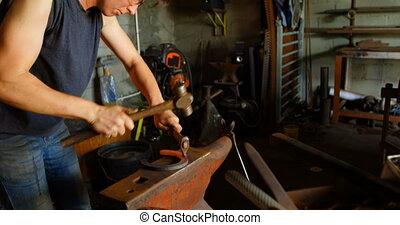 Female metalsmith molding horseshoe in factory 4k - Side ...