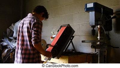 Female metalsmith using sharpening machine 4k - Rear view of...