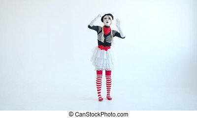 Female mime artist is knocking on imaginary wall gesturing standing on white background alone and looking at camera. Pantomime and emotions concept.