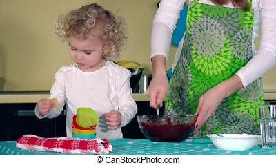 Female mixing chocolate dough with spoon and adorable helper daughter