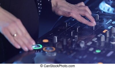 Female mixing music using DJ mixer, hands press the buttons