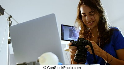 Female model looking at laptop and digital camera 4k -...