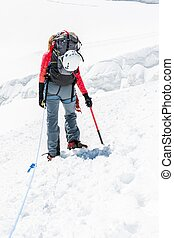 Female mountaineer ascending a glacier.