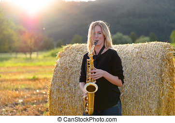 Female musician playing a tenor saxophone - Attractive...