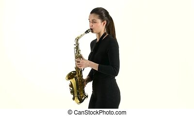 Female musician playing on saxophone standing sideways on...