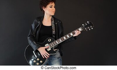 female musician playing the guitar in a black room