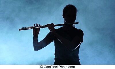 Female musician professional playing on flute. Smoky studio, slow motion