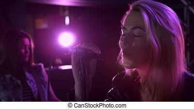 Side view close up of a Caucasian female singer performing at a music venue with a band, smiling and singing into a microphone, with pink lights and a musician in the background