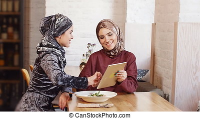 Female Muslim College Students Using Tablet Computer in Cafe.