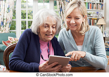 Female Neighbor Showing Senior Woman How To Use Digital...