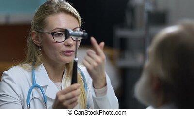 Female neurologist testing reflexes of eye of patient -...