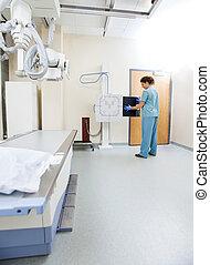 Female Nurse Adjusting Xray Film In Machine - Full length of...