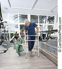 Female Nurse Assisting Senior Patient With Walker In Fitness Stu
