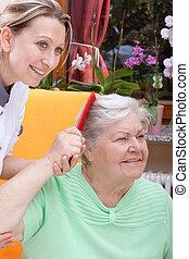 Nurse combs the hair of a senior