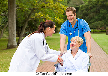 friendly female doctor or nurse greeting recovering senior patient in wheelchair outdoors