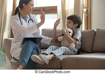 Female nurse have fun greeting with little patient