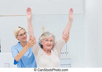 Female nurse helping female patient in exercising