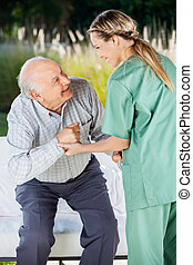 Female Nurse Helping Senior Man To Sit On Couch