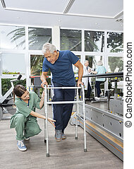 Female Nurse Helping Senior Patient With Walker In Fitness Studi