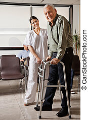 Portrait of senior man being assisted by female nurse to walk Zimmer frame with person sitting in background