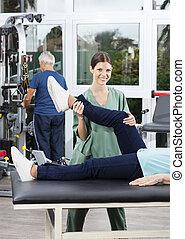 Female Nurse Helping Senior Woman In Leg Exercise