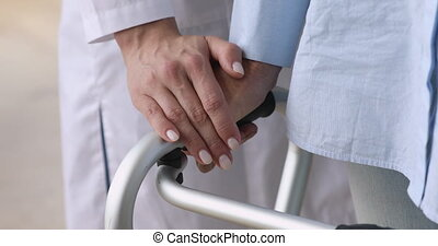 Female nurse holding old patient hand using walking frame, ...