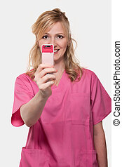 Female nurse holding up cell phone