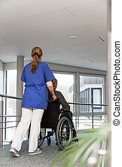 female nurse is sliding a man in a wheelchair