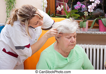 Nurse massages the head of a senior