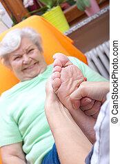 female Nurse massaging foot of a patient