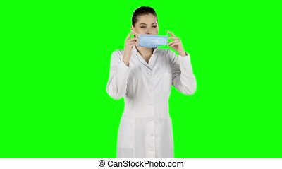 Female nurse puts on a blue medical mask. Green screen