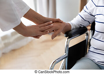 Female nurse take care of senior disabled woman patient