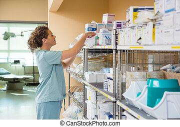 Female Nurse Working In Storage Room - Side view of female...