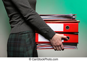 Female office worker carrying a stack of files - woman in ...