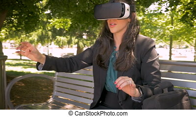 Female office worker experiencing virtual reality with VR headset outside