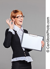 Female office worker gesturing perfect and holding a clipboard