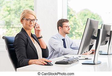 Female office worker in formalwear with her colleague