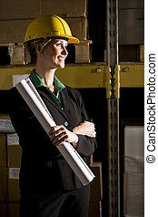 Female office worker in storage warehouse holding plans