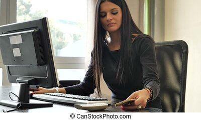 Female office worker sitting at desk busy with two phones