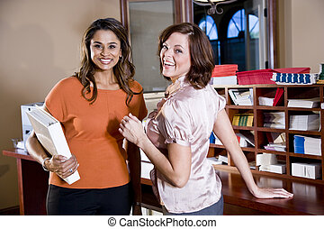 Female office workers chatting in copy room - Multiethnic...