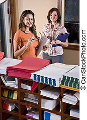 Female office workers standing in mailroom
