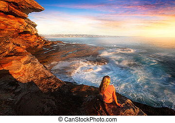 Female on rocks watching the ocean cascade around coastal rocks